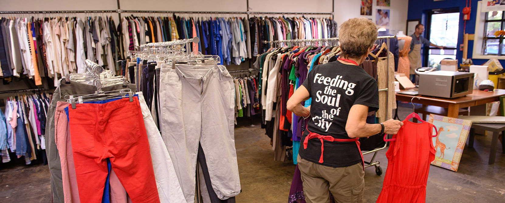 A Martha's Table volunteer stocks clothes at the organization's distribution center