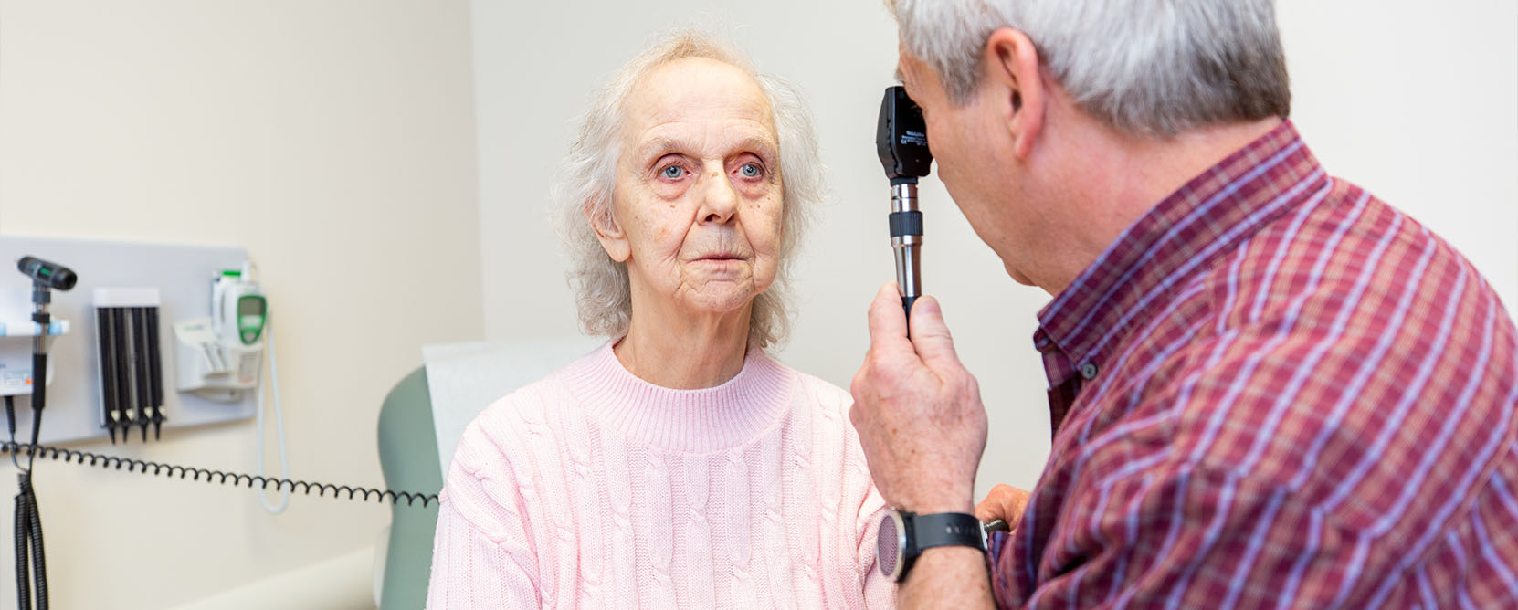 Older adult patient has her eyesight checked by a doctor