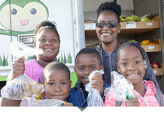 Mother stands with her four children holding bags of fruit in front of mobile farmers market