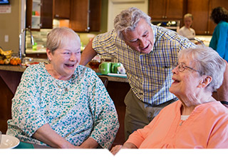 Three older adults talk and laugh at table.