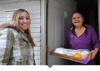 Volunteer delivers meal to older adult woman at her home