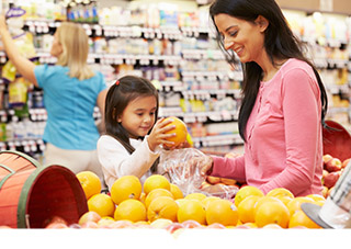 Small child putting orange in bag held by mother in produce aisle at grocery store