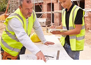Two construction workers on a construction site looking at architectural drawings