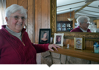 Older woman stands at mantle smiling and looking at pictures