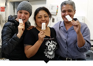 Three woman from Prospera Coop posing with funny faces eating popsicles