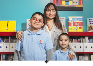 Mother poses with her two children inside of Equitas Academy Charter School classroom