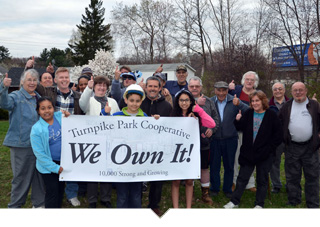 Large group of people pose together holding sign outside of the manufactured housing community that reads We Own It