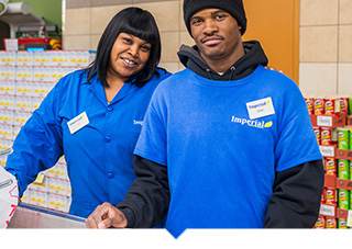 Two Imperial Fresh Market workers posing together inside grocery store in Detroit