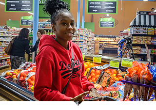 Woman shopping for produce at Imperial Fresh Market grocery store in Detroit