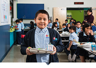 Equitas academy student holding lunch tray with healthy food in cafeteria in Los Angele
