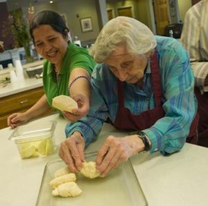 Two women baking dinner rolls