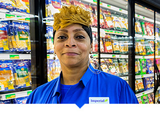 Imperial Fresh Market employee in Detroit poses in aisle of grocery store