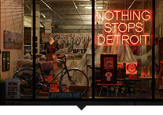 Neon sign in window of store that reads Nothing Stops Detroit