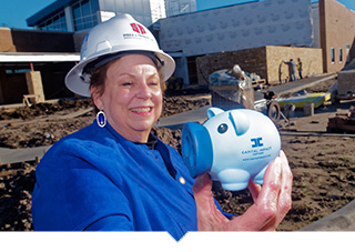 Meals on Wheels of Tarrant County CEO holds up Capital Impact Mascot PennyWise in front of construction site