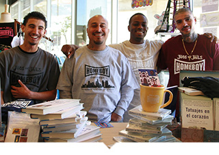 Four Homeboy Industry employees in Los Angeles pose with merchandise