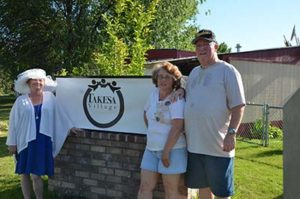 Three residents stand in front of Takesa Village community sign