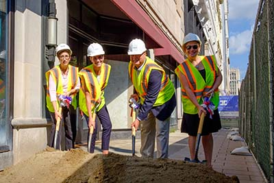 Four people dig shovels into a mound of dirt at the Elliott groundbreaking