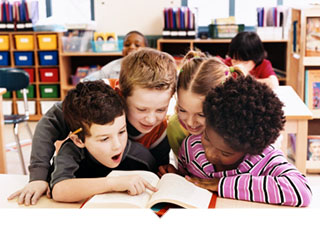 Four kids reading a book together in classroom