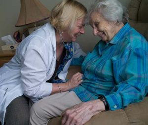 A nurse shares a laugh and a hug with her elderly female patient.