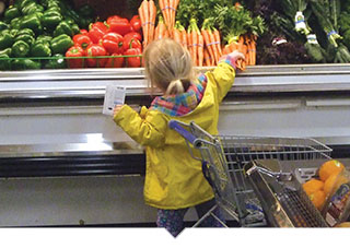 Little girl reaches up to grab fresh produce