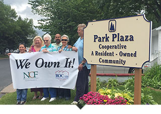 Group of cooperative homeowners hold We Own It sign
