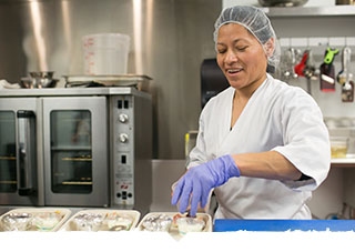 Female chef preps food in kitchen