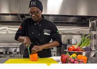 Female chef prepares food in professional kitchen
