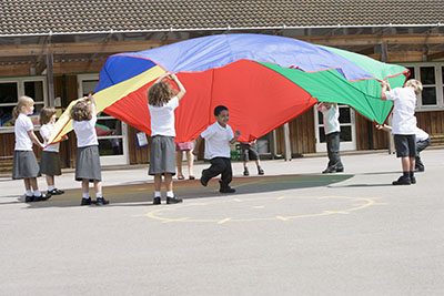 Young children playing with a parachute in the school playground