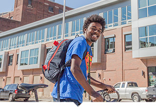 Young Man poses with bike outside of affordable housing complex