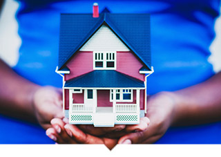 Close up of hands holding a model of a house