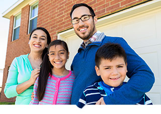 Mother and father with pre-teens pose in front of their home