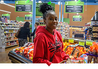 Young woman with Detroit sweatshirt shops at Grocery Store