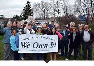 Homeowners pose with We Own It Banner