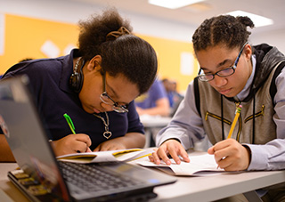 wo high-school students work together on an assignment.