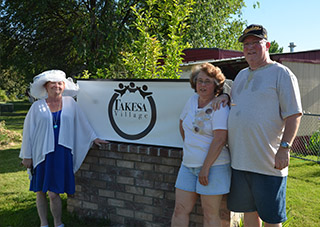 Residents pose with Takesa Village sign
