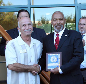 Two men shake hands and display plaque for health center opening