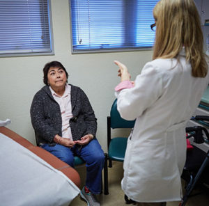 Older female patient listens to doctor