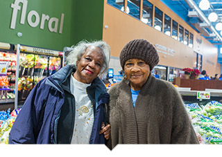 Two older women shop for produce