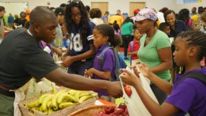 Volunteers help families choose produce; photo: KIPP DC