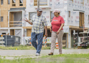 Detroit residents walk past renovated building in Detroit