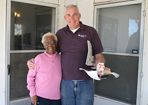 Volunteer with Meals on Wheels brings a meal to an older woman