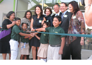 A group of adults and charter elementary school students cut the ribbon to celebrate a new school opening