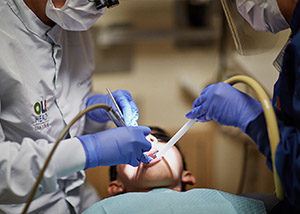 A dentist cleans a boys teeth.