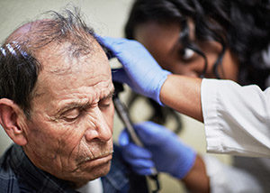 An older man receives a check-up at a clinic.