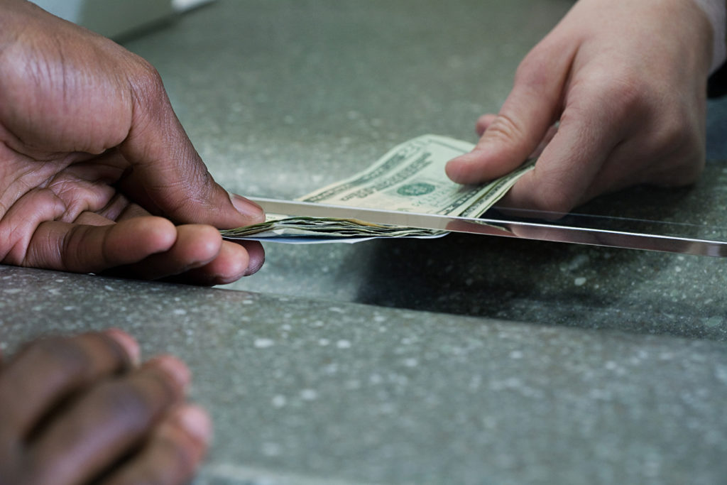 Bank teller hands money to a customer.