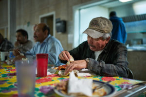 Men eat in a farmworkers' center in California.