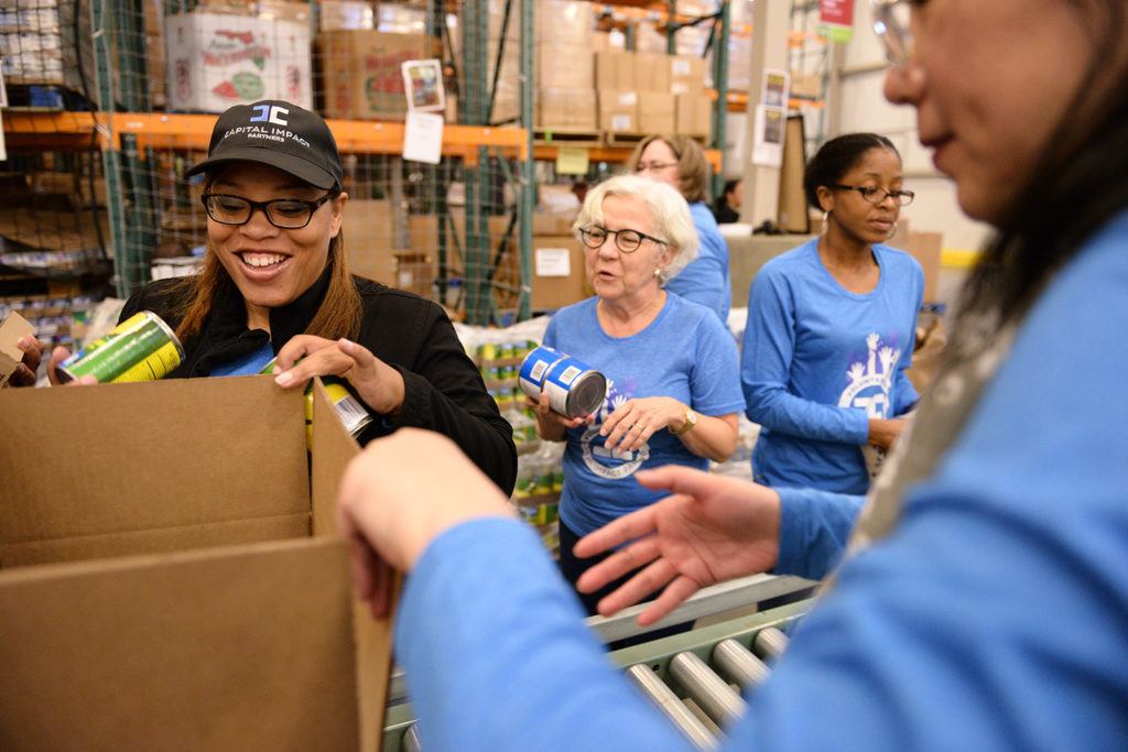 Capital Impact staff pack boxes with non-perishable food for families experiencing.