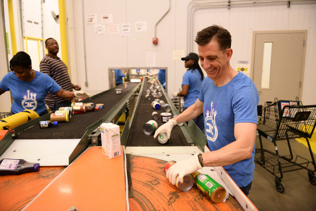 A Capital Impact employee helps sort canned goods on a conveyor belt.