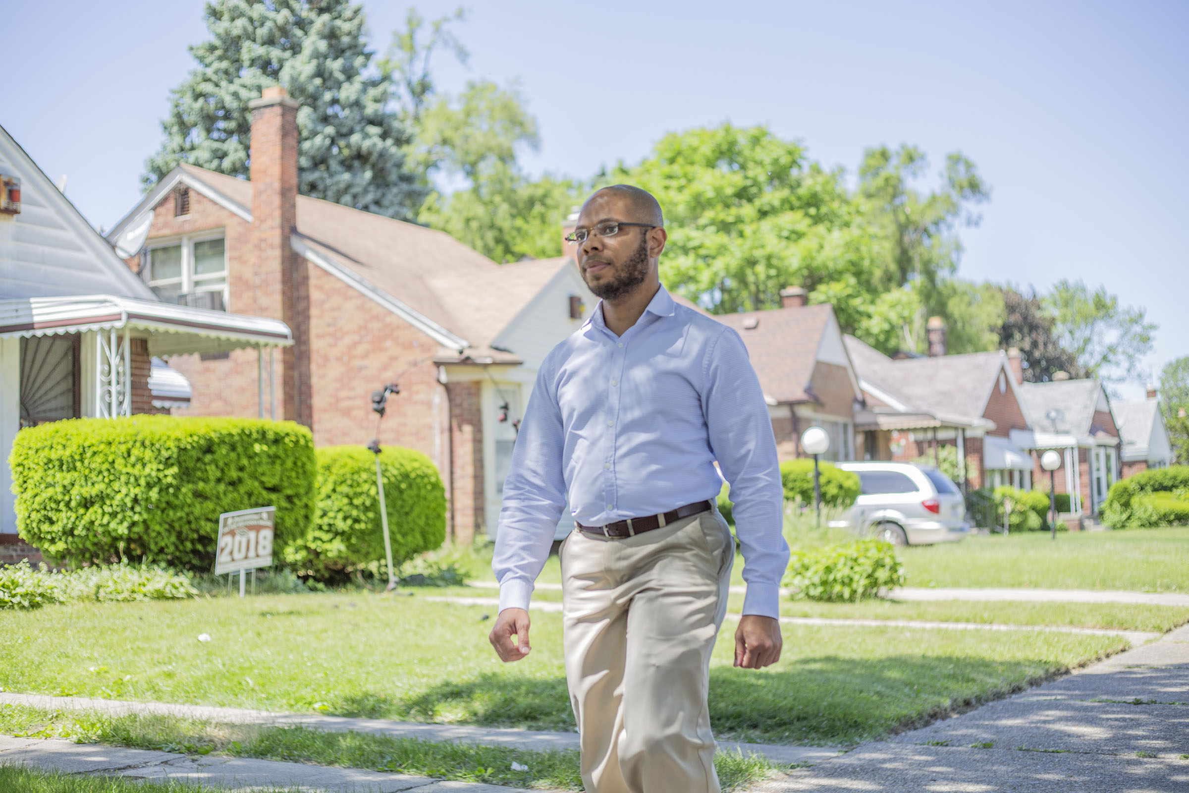 A man walks through a neighborhood
