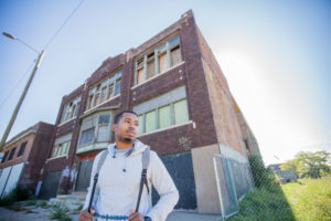 Young man in front of a boarded-up building
